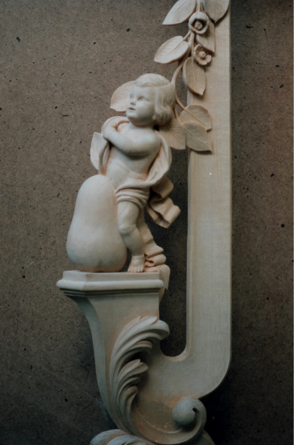 Close up showing left hand frame with pear cherub - pear hand carved mirror jose sarabia cherub