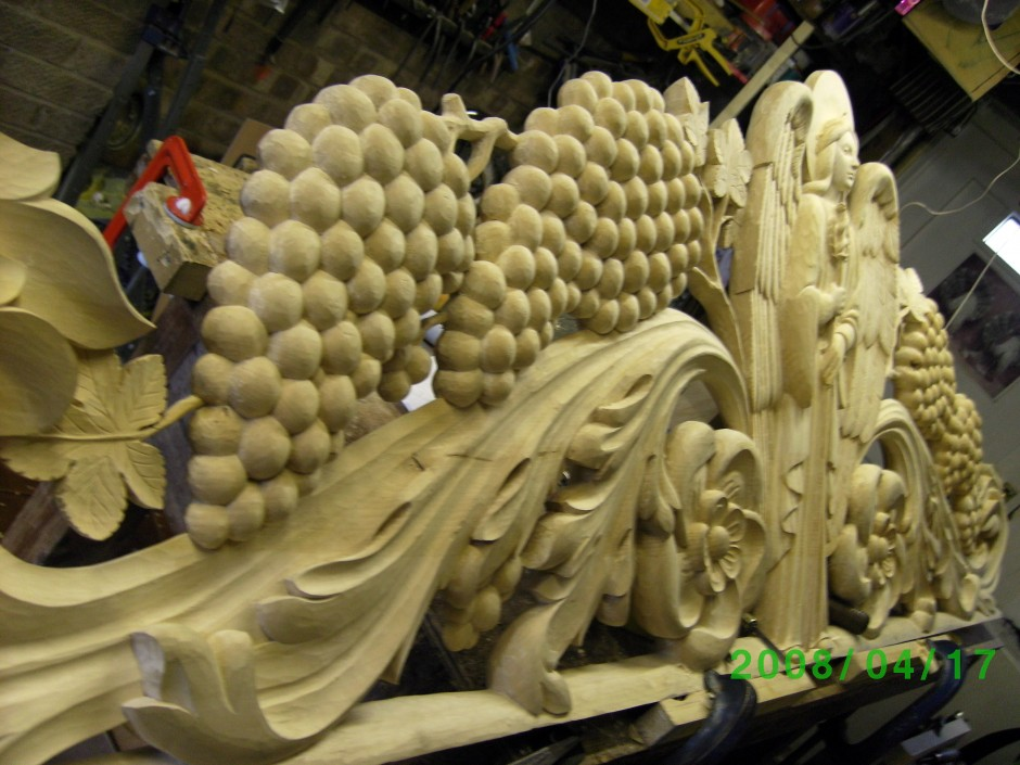 The bedhead, carving in progress in the workshop - bed head grapes leaves angel